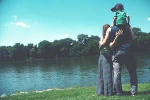 A family standing on the edge of a body of water