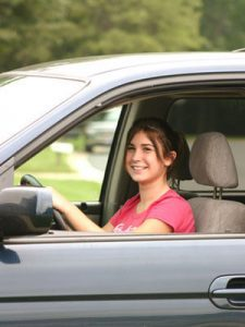 A young female in the driver side of a car representing a teen driver