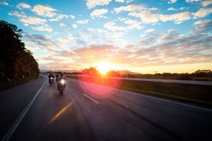 Motorcycle riders driving on a highway during sunset