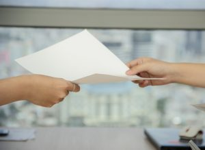 A person passing a piece of paper to another person