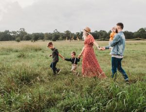 A family of five walking through a field of grass