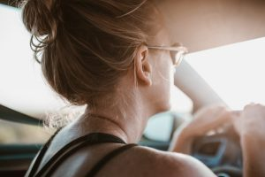 A woman driving a car while wearing sunglasses